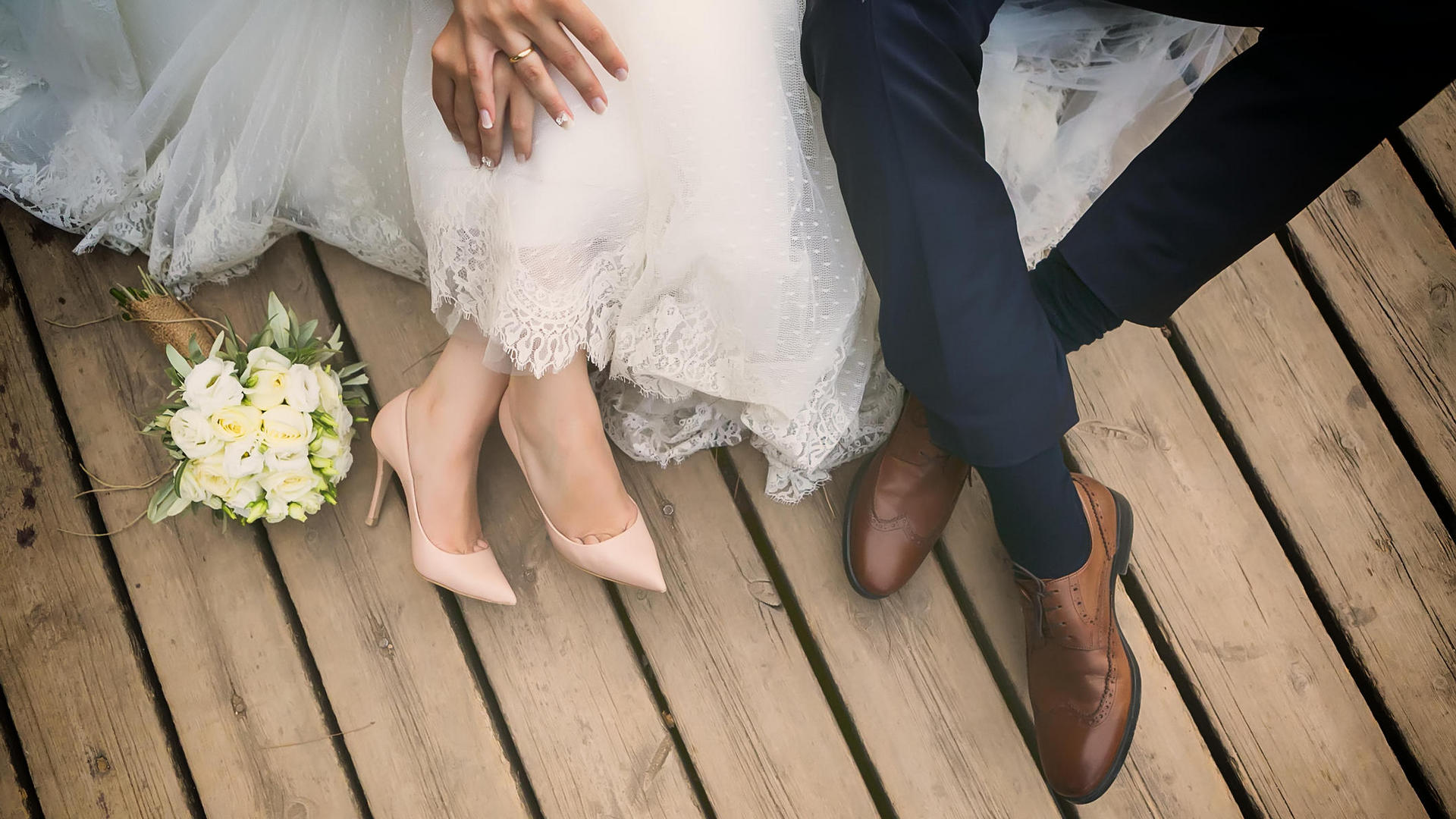 picture of bride and groom sitting on a dock