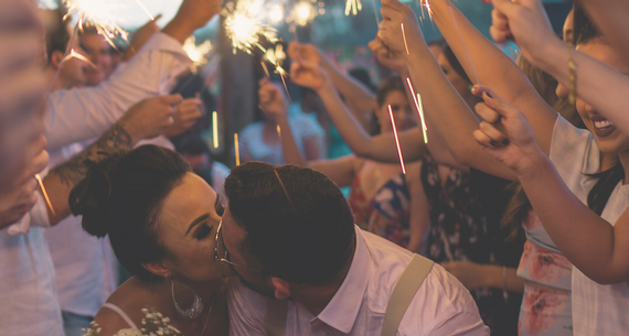bride and groom kissing under sparklers
