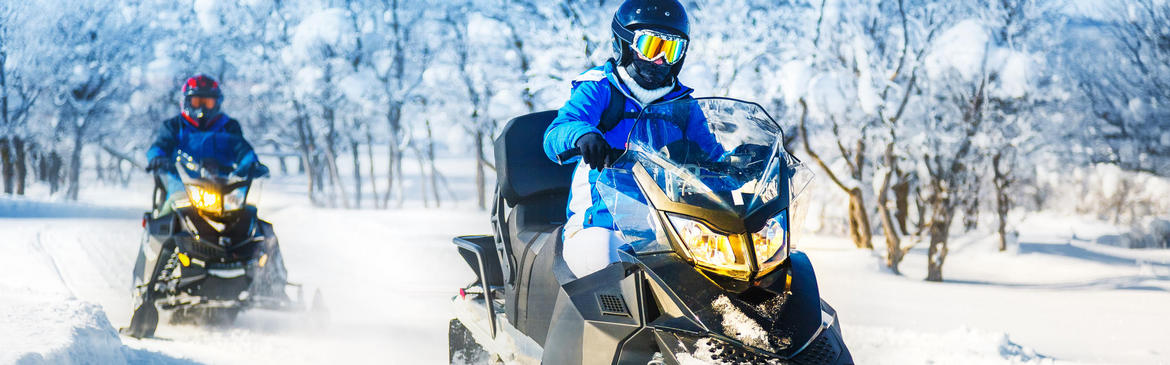 two people snowmobiling on groomed track