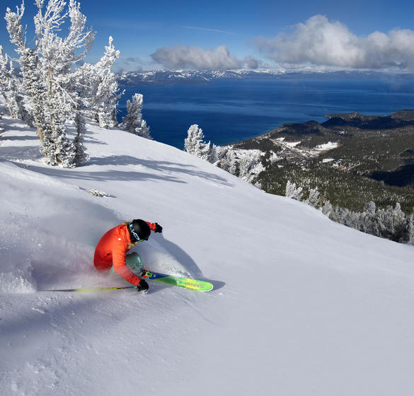 A guy snowboarding in the mountains surrounding lake tahoe